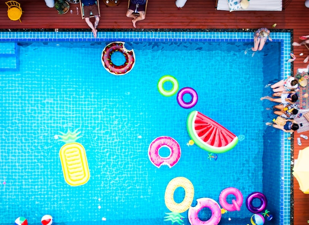 Aerial view of people enjoying the pool with colorful inflatable floats
