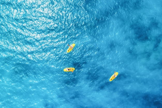 Aerial view of the people in kayaks in the blue sea
