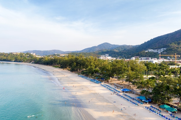 Aerial view of people swimming in the transparent turquoise sea at karon beach in phuket, thailand.