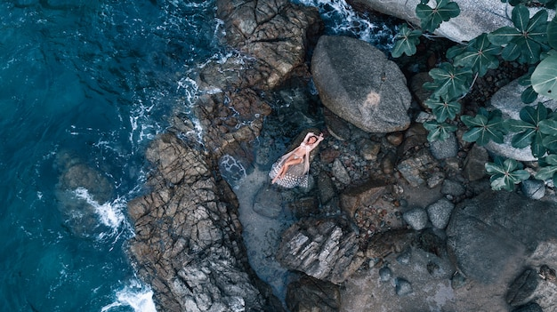 Aerial view: photo of a beautiful posing girl lying in a white dress, among the rocks near the sea.