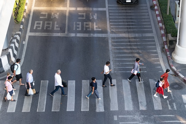 Aerial view photo of people walk on street in the city over pedestrian crossing traffic road