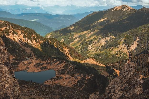 昼間の山々に囲まれた湖の空撮