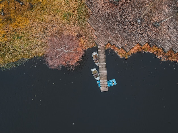 Aerial view pier with wooden boats on the shore of a picturesque lake, autumn forest. st. petersburg, russia.