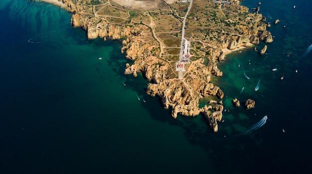 Vista aerea di ponta da piedade di lagos, portogallo. paesaggio di bellezza di aspre scogliere sul mare e acque oceaniche nella regione dell'algarve in portogallo