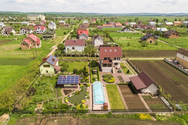 Aerial view of a private house in summer with blue solar photo voltaic panels on roof top and in the yard.