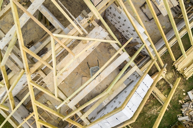 Aerial view of a private house with aerated concrete brick walls and wooden frame for future roof.