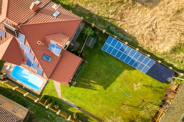 Aerial view of a private house with green grass covered yard, solar panels on roof, swimming pool and wind turbine generator.