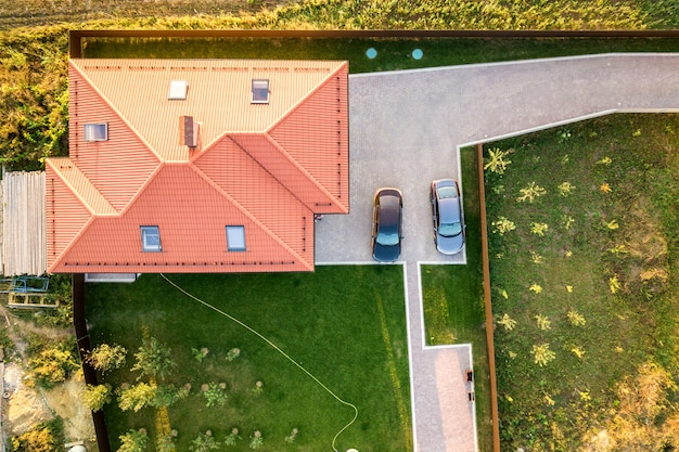 Aerial view of a private house with red tiled roof and yard with parked two cars.