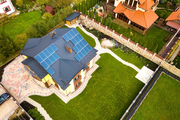 Aerial view of a private house with solar photovoltaic panels for producing clean electricity on roof. autonomous home concept.