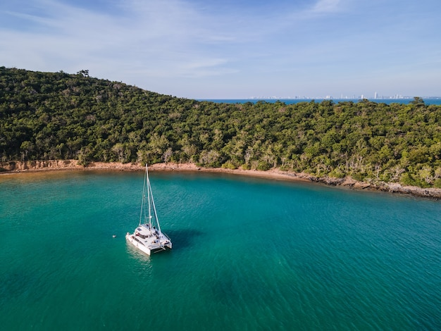 Aerial view of private yacht cruising on tropical sea at evening