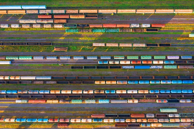 Aerial view of rail sorting freight station with railway cars, with many rail tracks railroad. heavy industry landscape on evening sunset light.