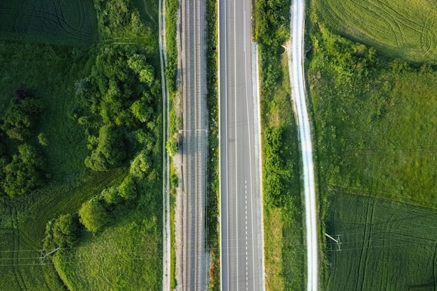 Aerial view, railway and road in rural landscape.
