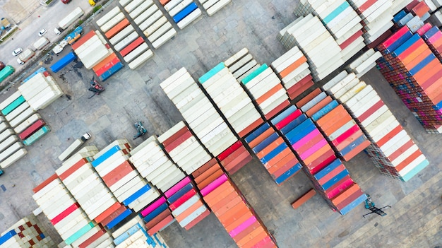 Aerial view reach stackers move containers at a freight terminal, industrial container terminal and storage containers area.
