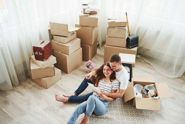 С высоты птичьего полета. чтение документа. веселая молодая пара в своей новой квартире. концепция переезда.