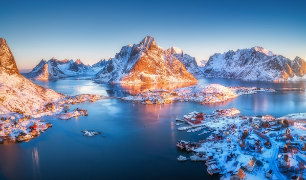 Aerial view of reine at sunrise in winter. top view of lofoten islands, norway. panoramic landscape with blue sea, snowy mountains, high rocks, village with buildings, rorbu, sky reflected in water