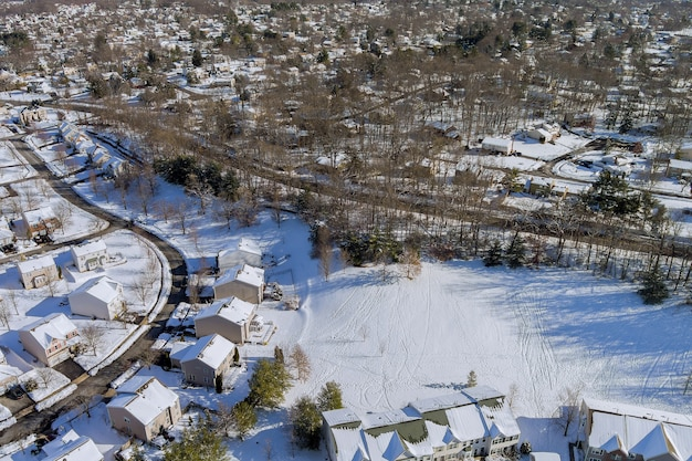 Aerial view of residential houses covered snow at winter season with snow on covered houses and roads.
