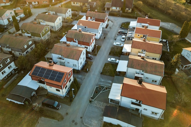 Aerial view of residential houses with red roofs and streets with parked cars in rural town area. quiet suburbs of a modern european city.