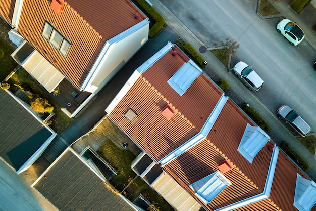 Aerial view of residential houses with red roofs and streets with parked cars in rural town area.