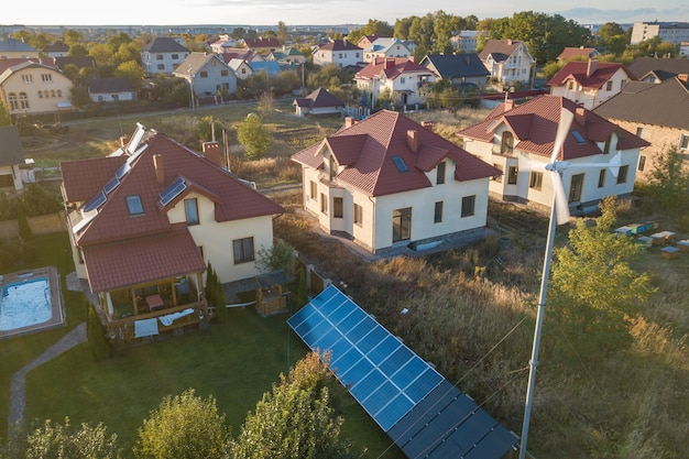 Aerial view of a residential private house with solar panels on roof and wind generator turbine.
