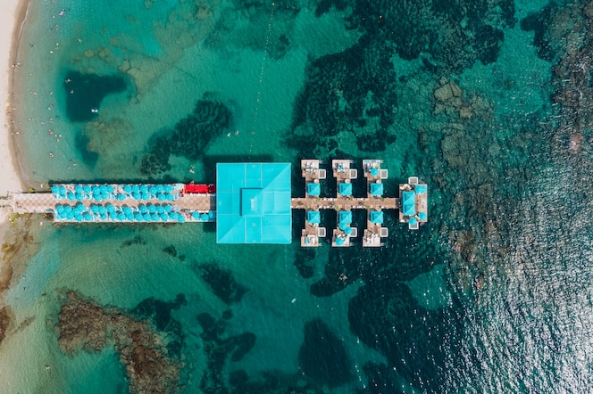 Aerial view of resort pierce in transparent sea water with rocks