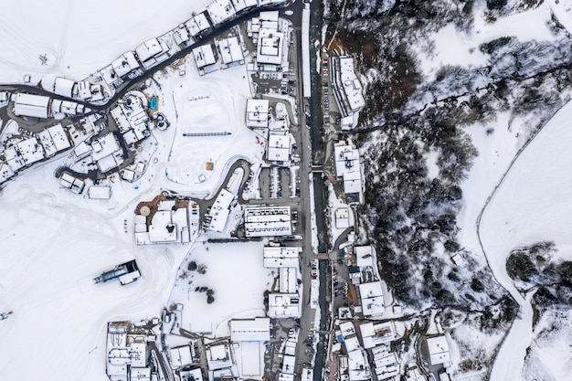 Aerial view of a resort town in austria surrounded by snowy mountains