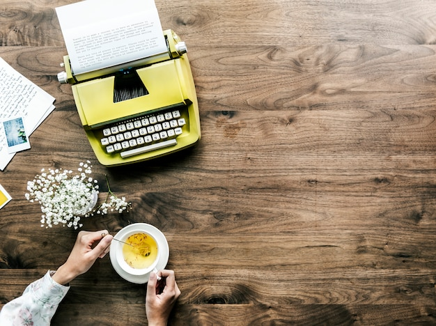 Aerial view of retro typewriter and a woman with a cup of tea