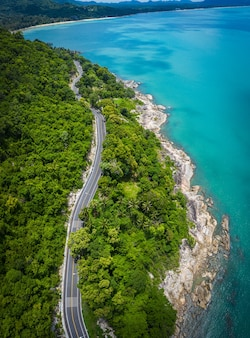 Aerial view of road between coconut palm tree and great ocean at daytime in nakhon si thammarat, thailand