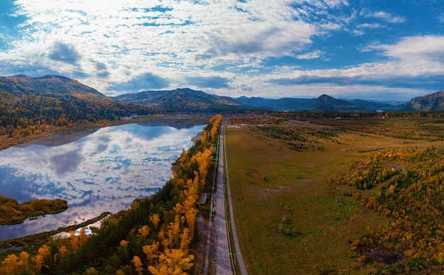 Aerial view of road and lake in beautiful autumn altai forest beautiful landscape with empty rural r... Premium Photo