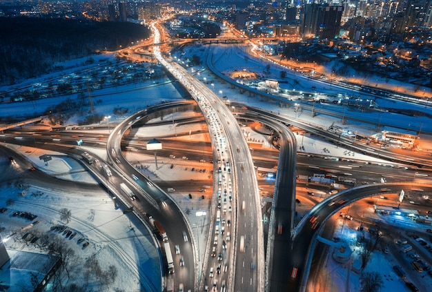 Aerial view of road in the modern city at night in winter. top view of traffic in highway, buildings, illumination.