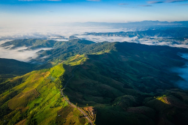 Aerial view road way on the green mountain peak in the rain season and morning mist and blue sky