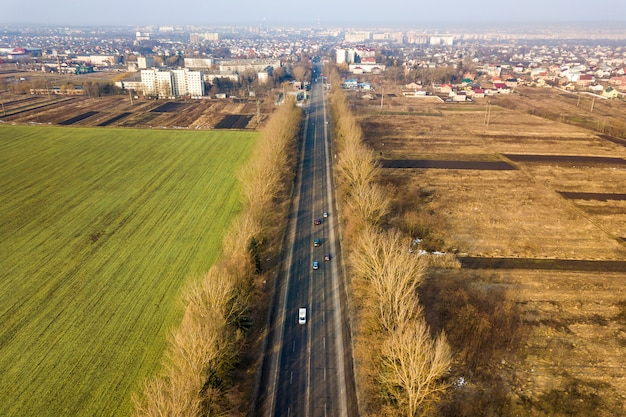 Aerial view of road with moving cars, green and plowed fields and meadow and city suburbs on sunny day. drone photography.