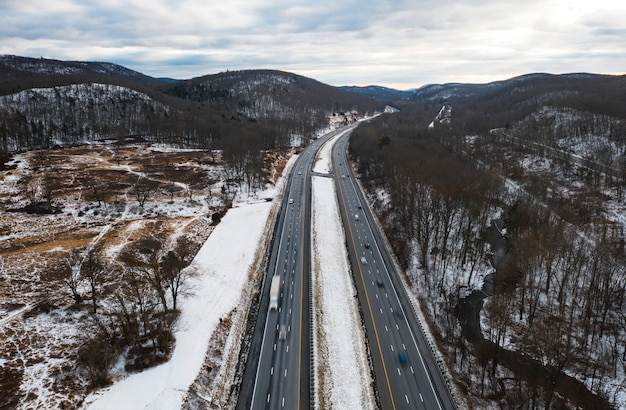 Aerial view of road with snowy forest