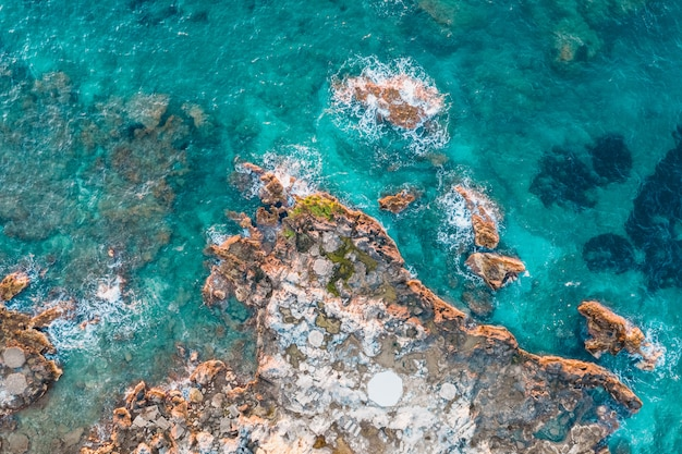 Aerial view of rocks under turquoise water