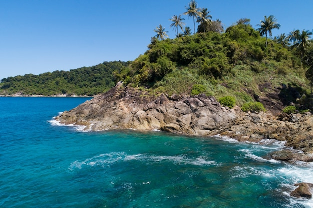 Aerial view rocky seashore under clear blue sky with clouds sea surface background beautiful sea amazing island in phuket thailand.