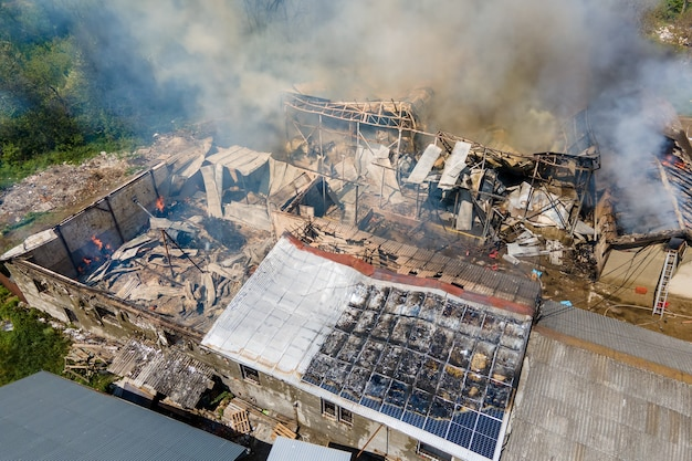 Aerial view of ruined building on fire with collapsed roof and rising dark smoke.