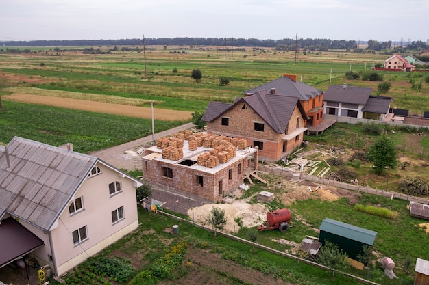 Aerial view of rural land for development in green field. new not finished brick houses and building sites