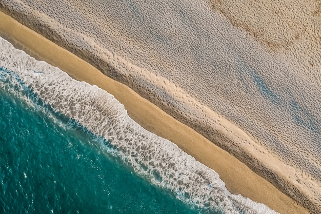Aerial view of sand meeting the sea water and waves