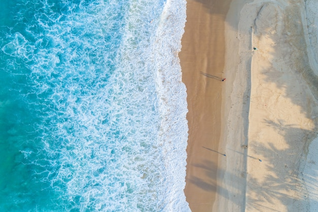 Aerial view sandy beach and waves beautiful tropical sea in the morning summer season image by aerial view drone shot, high angle view top down.