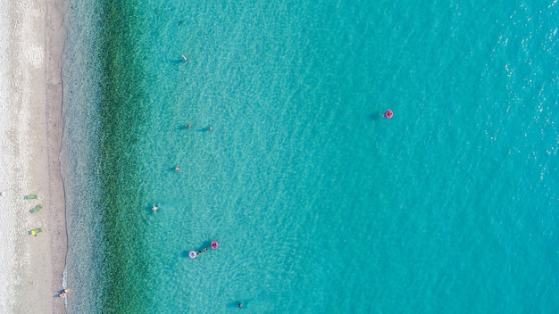Aerial view of sandy beach with tourists swimming.