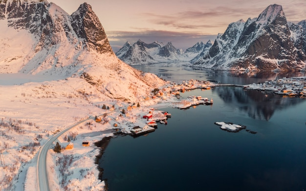 Aerial view of scandinavian village on coastline in snowy valley at sunset