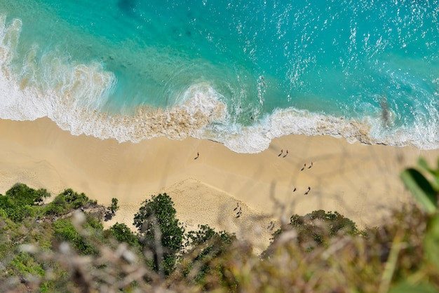 Aerial view of seascape blue ocean wave on sandy beach.
