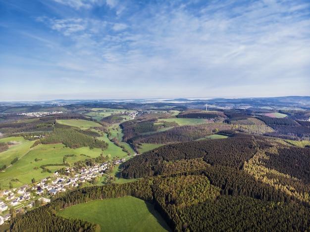 Colpo di vista aerea di bellissimi campi verdi e case di campagna in una giornata di sole
