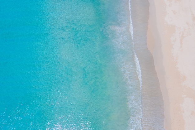 Aerial view shot top view drone camera over beach sand and sea water clear
