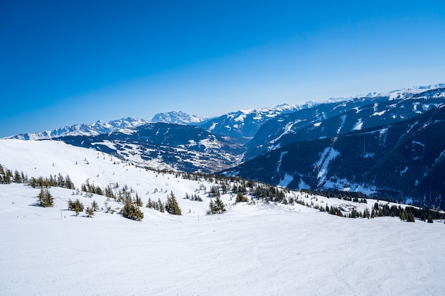 Aerial view of the skiers in a mountainous ski resort in the alps