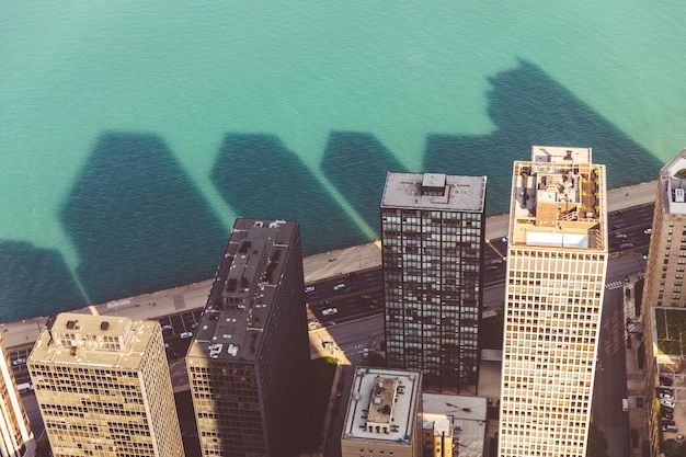 Aerial view of skyscrapers and their shadow on the water