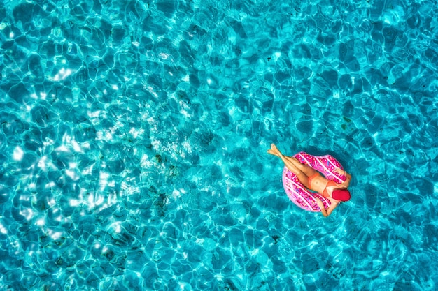Aerial view of slim young woman swimming on the donut swim ring in the transparent blue sea at bright day