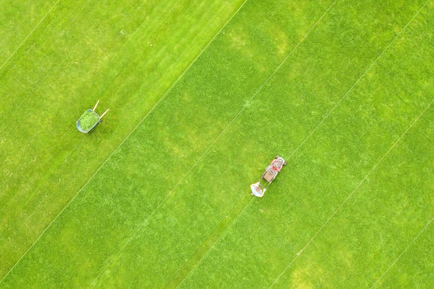 Aerial view of small figure of man worker trimming green grass with mowing mashine on football stadium field in summer.