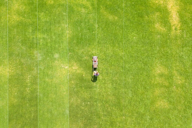 Aerial view of small figure of man worker trimming green grass with mowing mashine
