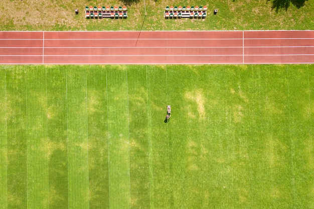 Aerial view of small figure of worker cutting green grass with mowing mashine on football stadium field with red running tracks in summer.