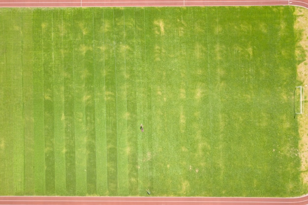 Aerial view of small figure of worker cutting green grass with mowing mashine on football stadium